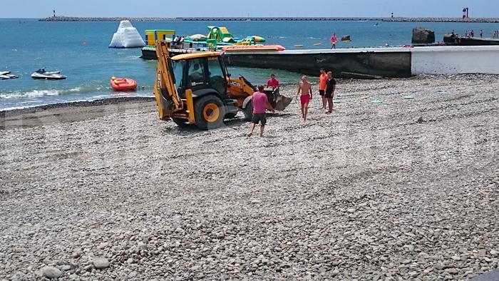 Трактор разравнивает щебень на пляже.