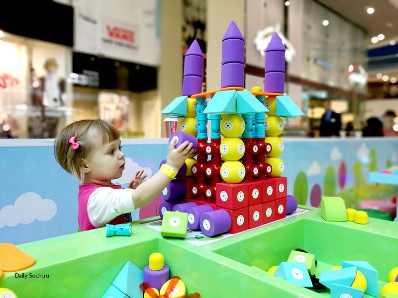 Девочка двух лет играет в конструктор