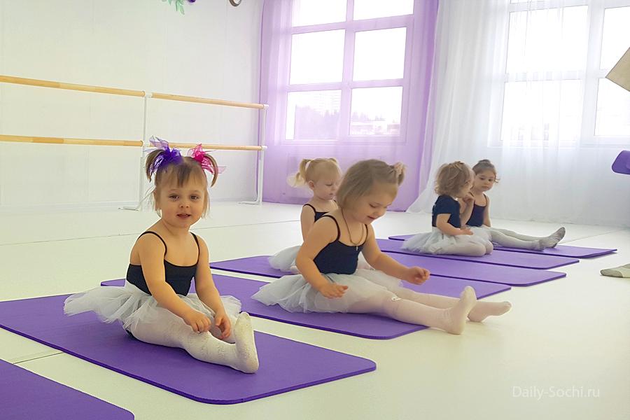 Балет в Сочи: малышки двух лет в балетных пачках сидят на ковриках в танцевальном зале.